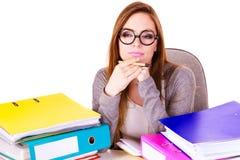 Donna che si siede allo scrittorio in ufficio e nel pensiero Immagini Stock