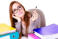 Donna che si siede allo scrittorio in ufficio e nel pensiero Fotografia Stock