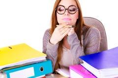 Donna che si siede allo scrittorio in ufficio e nel pensiero Immagini Stock Libere da Diritti