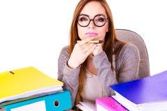 Donna che si siede allo scrittorio in ufficio e nel pensiero Fotografie Stock Libere da Diritti