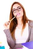 Donna che si siede allo scrittorio in ufficio e nel pensiero Fotografie Stock