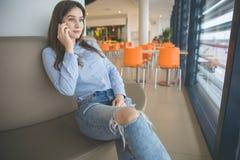 Donna che si siede allo strato del caffè che parla sul cellulare Immagine Stock Libera da Diritti