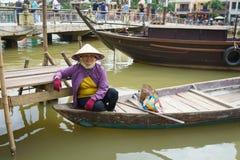 Donna che si siede in barca, Hoi, Vietnam fotografia stock