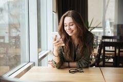 Donna che si siede in caffè fotografia stock libera da diritti