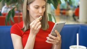 Donna che si siede in caffè facendo uso del suo smartphone, chiacchierante con gli amici che mangiano le patate fritte video d archivio