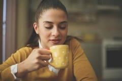 Donna che si siede a casa rilassamento con la tazza di caffè fotografia stock