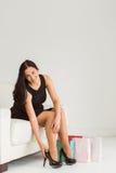 Donna che si siede con i sacchetti della spesa Fotografie Stock