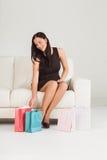 Donna che si siede con i sacchetti della spesa Fotografia Stock Libera da Diritti