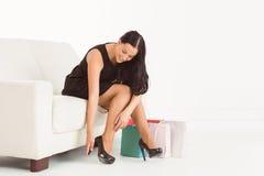 Donna che si siede con i sacchetti della spesa Immagine Stock