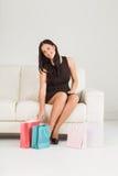 Donna che si siede con i sacchetti della spesa Immagini Stock