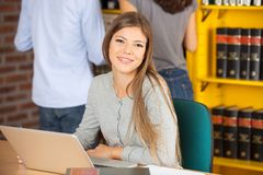 Donna che si siede con il computer portatile in biblioteca universitaria Fotografie Stock