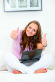 Donna che si siede con il computer portatile che mostra i pollici in su Immagine Stock Libera da Diritti