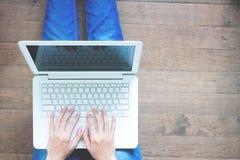 Donna che si siede con il computer portatile sul pavimento di legno, mani che scrivono messaggio a macchina, concetto di stile di Immagini Stock