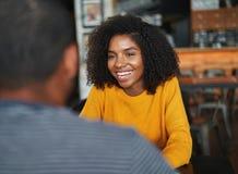 Donna che si siede con il suo ragazzo in caffè immagini stock