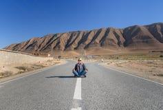 Donna che si siede con la gamba trasversale sulla strada Forcella nella strada morocco Fotografia Stock