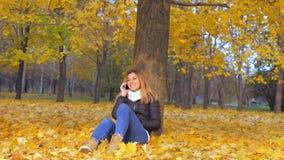 Donna che si siede con la sua di nuovo all'albero in Autumn Leaves giallo, Smartphone di conversazione Immagine Stock Libera da Diritti