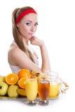 Donna che si siede con le spremute e la frutta fresche Fotografie Stock Libere da Diritti