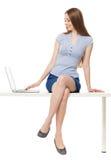 Donna che si siede con un computer portatile Immagine Stock