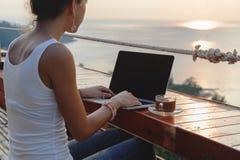 Donna che si siede con un computer portatile e una tazza di caffè davanti alla vista di tramonto Fotografia Stock Libera da Diritti