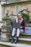 Donna che si siede con un computer portatile sul suo rivestimento Immagini Stock Libere da Diritti