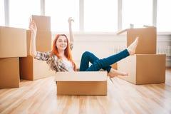 Donna che si siede in contenitore di cartone, inaugurazione di una nuova casa Fotografia Stock