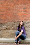 Donna che si siede contro un muro di mattoni immagine stock