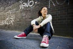 Donna che si siede contro un muro di mattoni Fotografie Stock Libere da Diritti