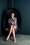 Donna che si siede in cuscinetto di tocco di funzionamento della sedia della bolla Immagini Stock