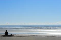Donna che si siede da solo alla spiaggia Fotografia Stock
