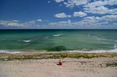 Donna che si siede da solo su una spiaggia nell'estate fotografia stock