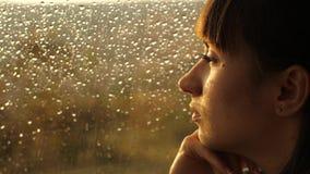 Donna che si siede da solo vicino alla finestra con le gocce di pioggia archivi video