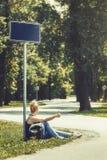 Donna che si siede da un lato della strada nell'ambito del segnale stradale, circondato dagli alberi, facenti auto-stop Immagini Stock Libere da Diritti