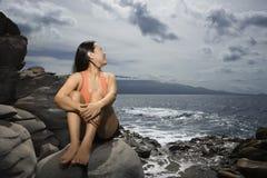 Donna che si siede dall'oceano immagini stock libere da diritti
