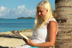 Donna che si siede dalla palma e che legge un libro Fotografie Stock
