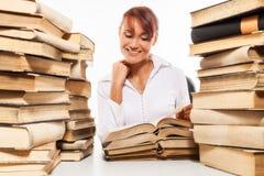 Donna che si siede dallo scrittorio con il mucchio dei libri Fotografie Stock