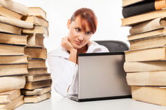 Donna che si siede dallo scrittorio con il mucchio dei libri Fotografie Stock Libere da Diritti
