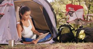 Donna che si siede dentro la tenda e che per mezzo di una compressa digitale archivi video