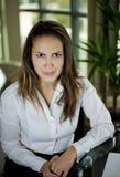 Donna che si siede dietro uno scrittorio Fotografia Stock Libera da Diritti