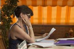 Donna che si siede esaminando una serie di documenti nel pomeriggio Fotografia Stock Libera da Diritti