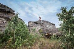 Donna che si siede fornito di gambe trasversale su una su un grandi formazione rocciosa e rilassamento dell'arenaria Fotografie Stock Libere da Diritti