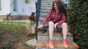 Donna che si siede fuori della casa con il gatto video d archivio
