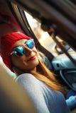 Donna che si siede nel sedile del passeggero dell'automobile Enjoyi dell'adolescente dei pantaloni a vita bassa fotografia stock libera da diritti