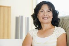 Donna che si siede nel sorridere del salone fotografia stock libera da diritti
