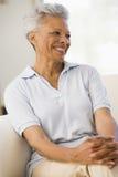 Donna che si siede nel sorridere del salone Immagine Stock Libera da Diritti