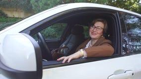 Donna che si siede nel sorridere dell'automobile video d archivio