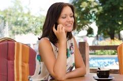 Donna che si siede nel suo giardino usando un mobile Fotografia Stock