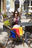 Donna che si siede nel terrazzo del caffè con i sacchetti della spesa facendo uso del telefono Immagine Stock