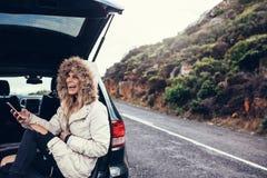 Donna che si siede nel tronco di automobile con uno Smart Phone Immagine Stock Libera da Diritti