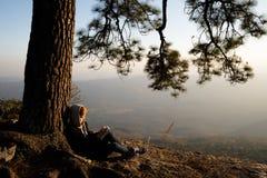 Donna che si siede nell'ambito della lettura e della scrittura del pino immagini stock