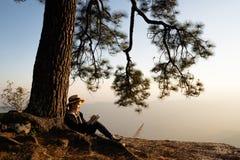 Donna che si siede nell'ambito della lettura e della scrittura del pino immagine stock libera da diritti
